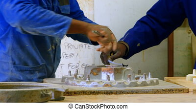 Workers discussing over metal casting mold in workshop 4k - ...