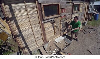 Workers dismantle and demolish the old wooden house. 4K.