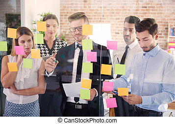 Workers focused on colorful adhesive notes