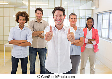 Workers giving thumbs up to camera in the office