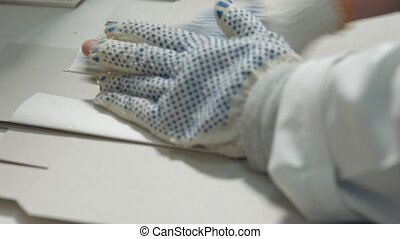Worker's hand making paper box.