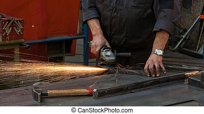 Workers\' hands in the metal industry with cutter