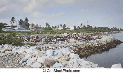 Workers hauling garbage around the site of a local landfill, along a polluted section of coast on Maafushi Island, Maldives. UltraHD stock footage