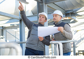 workers holding blueprints and looking