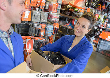 Workers holding cardboard boxes in hardware store