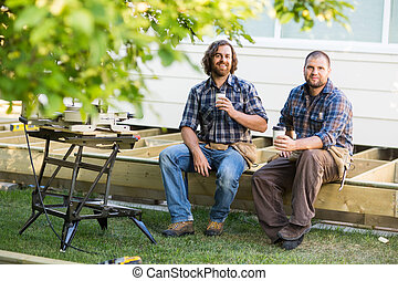 Workers Holding Disposable Cups While Sitting On Wooden Frame