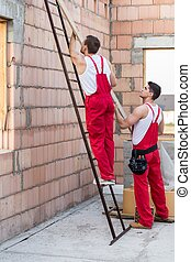 Workers holding wooden balk - Picture of two construction ...