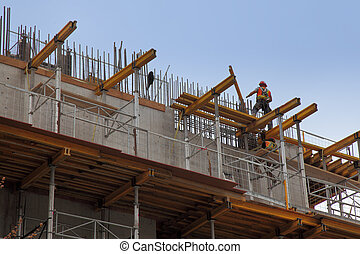 workers in action during construction of a steel beam office building