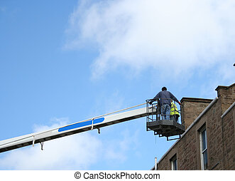 workers in cherry picker inspecting roof