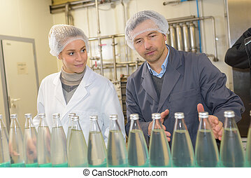 workers in factory checking water bottles
