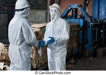 Workers in Hazmat Suits Communicating at Factory