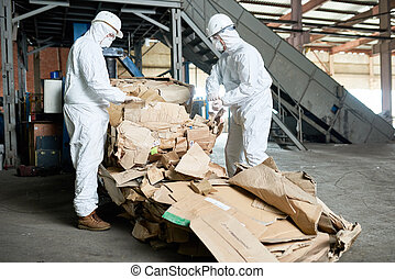 Workers in Hazmat Suits Sorting Cardboard at Modern Factory