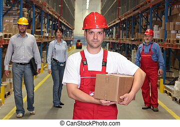 workers in warehouse - worker in hardhat with parcel at the...