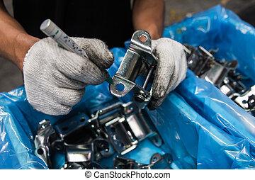 Workers inspect automotive parts.