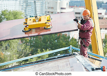 workers installing glass window on building