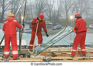 workers installing glass window on building - three builders...