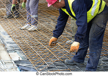 Workers installing reinforcement mesh - Construction workers...