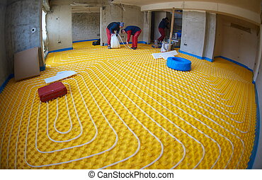 workers installing underfloor heating system - grouo of...