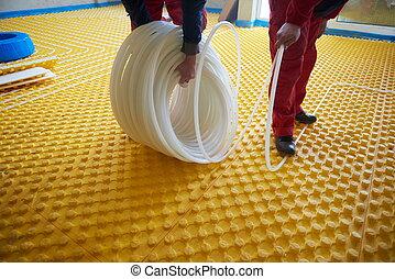 workers installing underfloor heating system - grouo of...