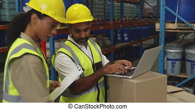 Workers interacting in a warehouse - Side view close up of a...