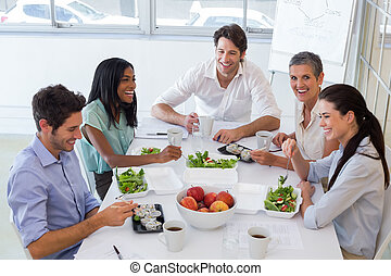 Workers laughing while enjoying lunch break in the office