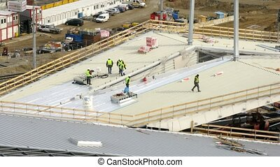 Workers lay an insulating cover on roof