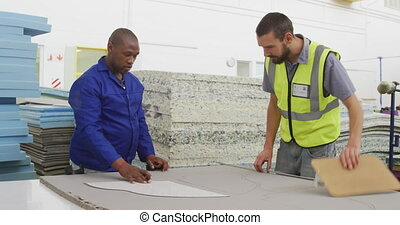 Workers looking at a pattern on a cardboard