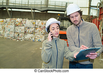 workers looking at clipboard and using telephone in...