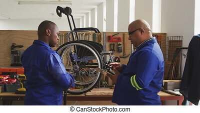 Workers making a wheelchair - Side view of a mixed race and ...