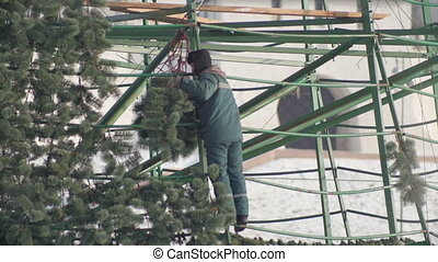 Workers making construction for new year pine celebrate, clode up