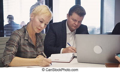 Two ambitions and successful businessperson with calm face sitting inside office with loft interior working place. Man and woman making research and notes about testing new startup project