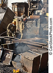 Workers melting metal