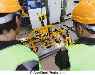 Workers near metal sheet lifting device