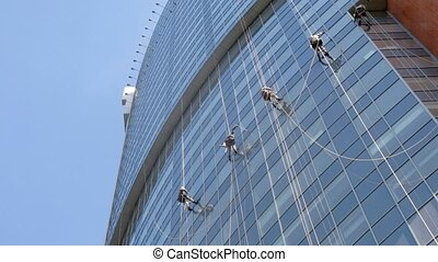 Workers of special company clean skyscraper windows, time...