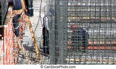 Workers on a construction site set reinforcement for concrete pouring