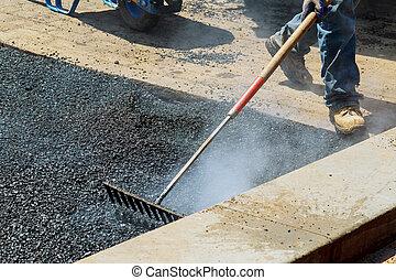 Workers on Asphalting paver during Road street repairing works.