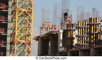 Workers on building carcass, blue sky at background