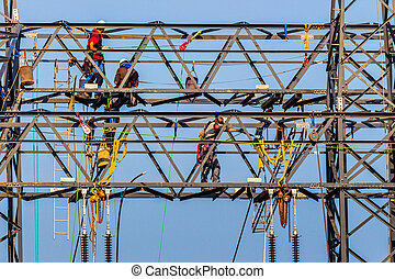 power line will be built - workers on electricity poles. a ...
