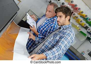 workers on large printer format inkjet working