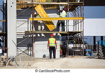 Workers on scaffolds - Team work at construction site, ...