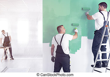 Workers painting wall on green while standing on ladder while finishing interior