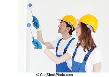Workers painting wall