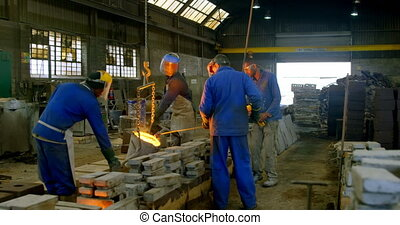 Workers pouring molten metal in molds at workshop 4k