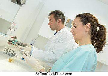 Workers preparing dental equipment