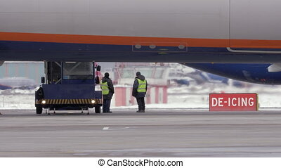 Long shot of two workers preparing to de-ice a jet plane on the runway