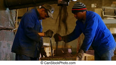 Workers putting soil in metal mold in foundry workshop 4k - ...