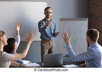 Workers raising hands asking questions during team meeting