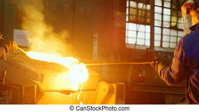 Workers removing metal from furnace in workshop 4k - Workers...