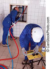 Workers  repairing pipes