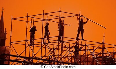 workers silhouette at sunset builders collect the design....